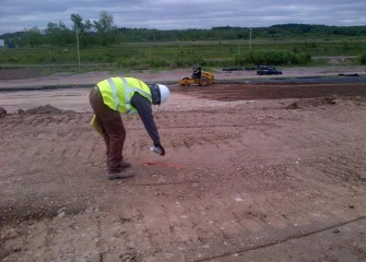 A worker prepares to test compaction of the leveling layer, which averages four feet thick.