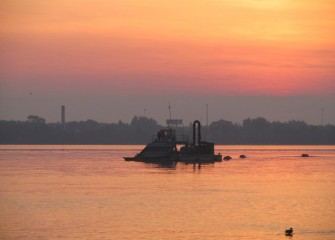 A hydraulic capping barge on Onondaga Lake near sunrise.