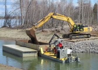Capping material is loaded into a barge at Nine Mile Creek for placement in the lake.