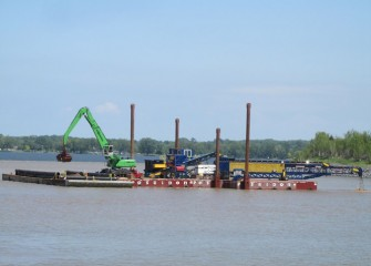 A telescoping radial stacking conveyor, or telestacker (right), is installed on a barge to assist in capping operations.