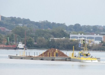 A tugboat pushes a delivery of material for mechanical capping.