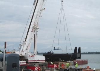 A hydraulic truck crane is used to lift a section of a tug boat into the water.