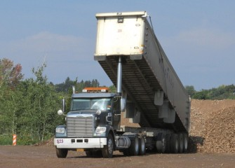 A load of coarse gravel arrives to a capping support area.