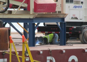 A welder works on an additional barge being assembled for capping operations.