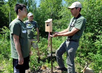 Montezuma Audubon Center Director Chris Lajewski (right) explains to Josh Zhao (left) and Richard Blankenship that the height and placement of a nest box is as important as the dimensions of the box itself to attract target species.
