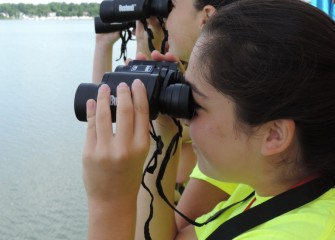 Emma Garvey (background) and Kaitlyn Jaeger, from West Genesee School District, try to spot waterbirds and shorebirds.