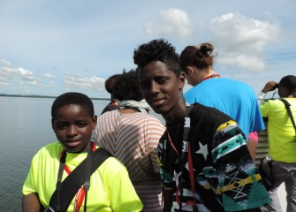 Isaac Kizza (left) and Abdi Hassan, from Syracuse City School District, enjoy starting out the week on a boat tour of the lake.
