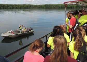 A SUNY-ESF research boat pulls up alongside the Emita II to show students fish just caught in Onondaga Lake.