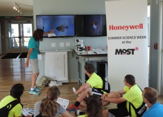 Honeywell Educator Sue Potrikus uses a special projector to show living microscopic zooplankton and phytoplankton in a sample of water just taken from the lake.