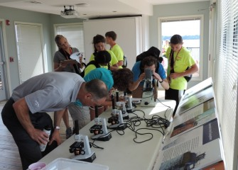 John McAuliffe (left) participates with students as they observe living microorganisms from the lake.