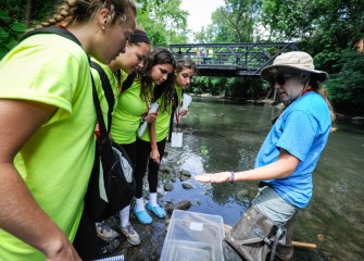 Counselor Renee Halloran (right) describes macroinvertebrates found in the creek, such as mayflies, freshwater shrimp, and aquatic worms.