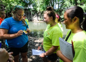 Students Maggie Muldoon (center) and Julia Commane (right), from Liverpool School District, learn how to measure the water's pH using test strips.