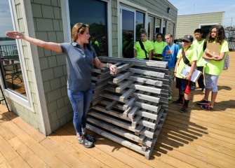 "Anne Burnham, Associate Scientist at Parsons, shows students a ""porcupine crib,"" a structure that will be sunk into the lake to provide additional fish habitat."
