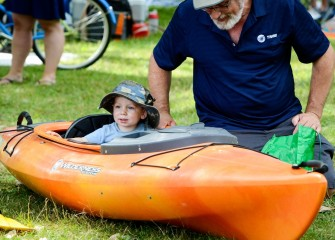 Sixteen-month old Christopher takes a ride in a kayak on land with his grandfather Charles Bertuch, of Syracuse.