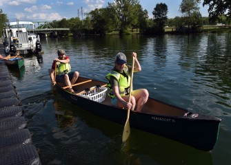 Rick Betty and Cari Brazie, from Brewerton, push off to head down Seneca River where most of the water chestnut will be pulled.