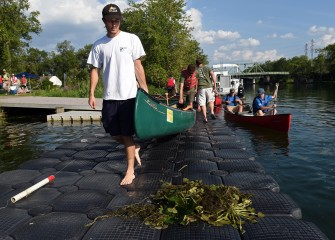 Nick Glaza (left) and his father Ed, of Skaneateles, carry their canoe out to launch, passing by sample water chestnut plants on the dock.