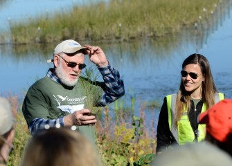 Corps volunteers Joe McMullen, habitat expert, and Natalia Cagide-Elmer, environmental engineer at Parsons, brief volunteers on native species they will plant in the new wetlands.