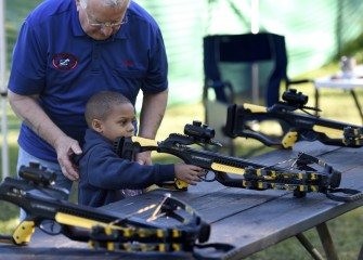 Onondaga County Federation of Sportsmen volunteers coordinate efforts among a number of local clubs to promote their outdoor sporting disciplines. Here 5-year-old Mason Wright learns how a crossbow works.