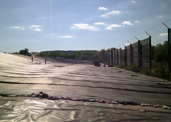Installation and sealing of the geomembrane, or cover liner, continues.
