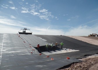 Polyethylene liner is unrolled down a slope of the consolidation area. The liner is 40 mil (thousandths of an inch) thick, a little over one millimeter.