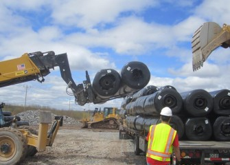 Work resumes covering the consolidation area. Rolls of geocomposite drainage net are unloaded and stacked at the site.