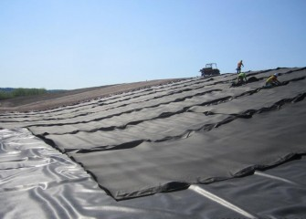 A layer of geotextile is laid on top of the leveling layer as a cushion and additional protection for the liner. The polyethylene liner is placed on top of the geotextile.