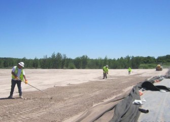 The surface of the leveling layer is raked by hand before cushion and liner placement.