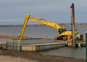 A long reach excavator is used to create a berm, forming a wetland area along the Western Shoreline.