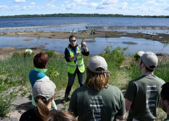 An environmental engineer with Parsons, Natalia Cagide-Elmer, explains proper planting procedures and goals for the day.