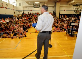 Honeywell Syracuse Program Director John McAuliffe speaks to students at East Syracuse Elementary's final assembly of the school year before presenting a flight suit.