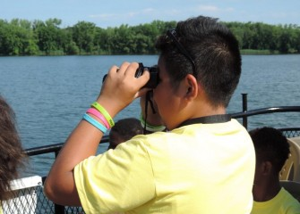 Rawri Da, from the Syracuse City School District, uses binoculars to spot birds in the water and along the shoreline.