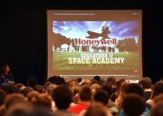 Students at Liverpool Middle School watch a video about Honeywell Educators @ Space Academy during an assembly.