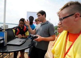 On Friday, Honeywell Day, environmental engineer Michael Smith (center) shows students operation of the Z-boat from the deck of the Onondaga Lake Visitors Center.