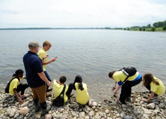 Students sample water along the Onondaga Lake shoreline.