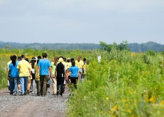 A group of students goes on a guided habitat walk in restored grassland, wetland, and shore areas along the western shoreline of the lake.