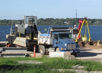 A support boat no longer needed in operations is removed from Onondaga Lake.