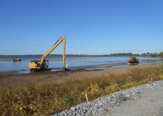 A long stick backhoe places topsoil along the southwestern shoreline.