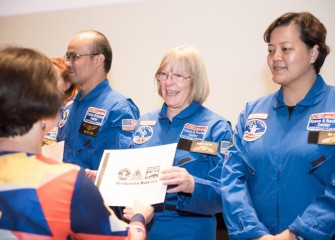 Colleen O'Connor from Roxboro Road Middle School receives a certificate and other materials during a graduation ceremony at Honeywell Educators at Space Academy.