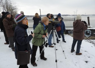 Paul Richardson (left) of Onondaga Audubon Society sets up a scope to help spot birds. Sue Fillinger (center) of Pompey sees a Great Black-backed Gull on the lake.