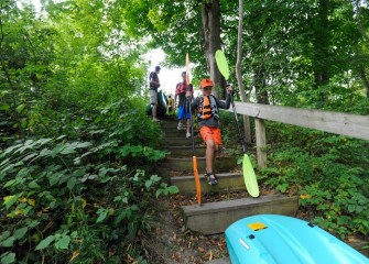 Grant Clift, age 8, from Baldwinsville, carries kayak paddles down to the creek shoreline.