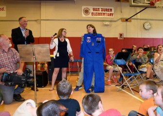 Teacher Sarah Parrish (center), selected to attend Honeywell Educators at Space Academy in 2017, is presented her flight suit at Van Buren Elementary School.