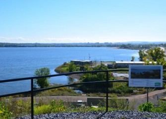 A view of the Onondaga Lake Visitors Center (center) and the City of Syracuse (background) from Onondaga County's West Shore Trail.
