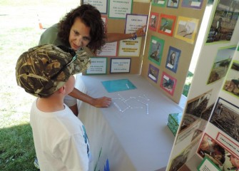 Sue Potrikus, coordinator for the Onondaga Lake Conservation Corps, works on a bird matching game with a visitor to her booth.