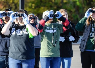 Members of the Binghamton University chapter of Alpha Phi Omega, a national coeducational service organization, observe birds in nearby trees.