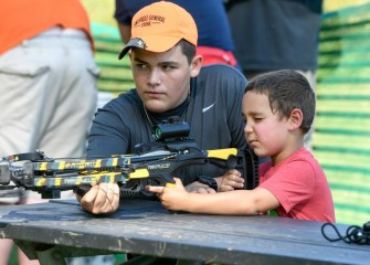 Fifteen-year-old New York Crossbow Coalition volunteer Tanner Hayes, of Hannibal, teaches 5-year-old Gabriel Rodriguez, of Clay, to use a crossbow.