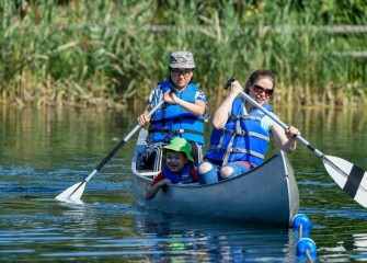 Pam Hartsell (front) and Liz Li, both of Fayetteville, give 6-year-old Jonah Hartsell a canoe ride.