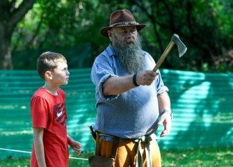 Ten-year-old Joey Cesario, of Auburn, learns how to throw a hatchet from New York State Muzzleloaders Association President Dan Fullington.