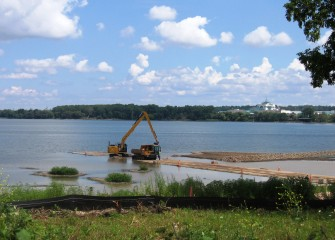 Topsoil is placed in shallow water areas, creating a habitat layer for underwater vegetation.