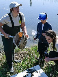 """The Young Naturalists Leadership Team creates opportunities to connect the Central New York community to conservation, restoration, environmental education, and stewardship projects,"" said Young Naturalists Leadership Team Project Coordinator Shannon Fabiani, pictured above, right, with Schermerhorn, helping 7-year-old Josh Gates (center) identify plant and animal species. ""We are excited to work with the Onondaga Lake Conservation Corps to inspire environmental stewards throughout our community."""
