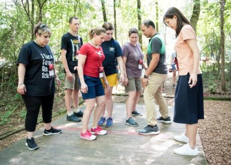 Michelle Hall (center, in red) on Day 1 with other Honeywell Educators on the low ropes course, where groups engage in team-building exercises.